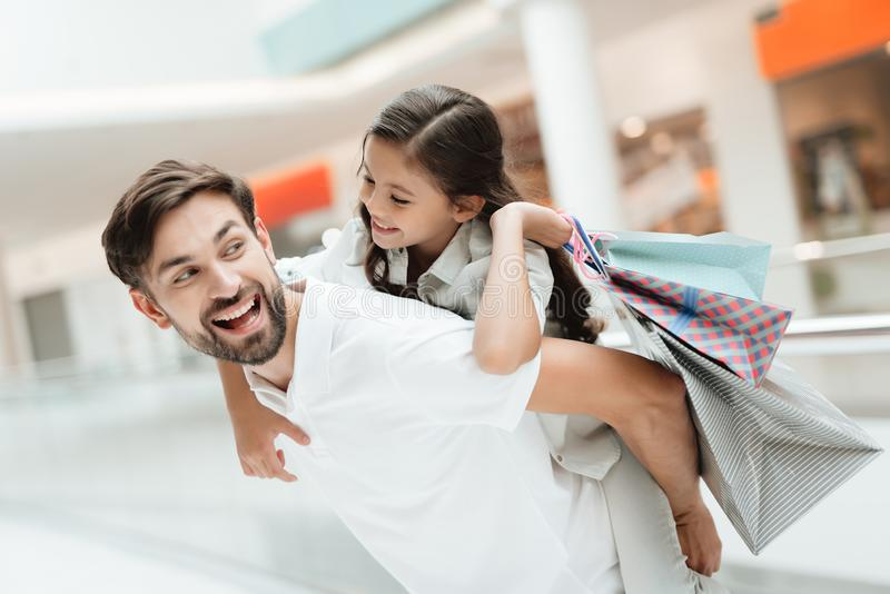 Father carries daughter on back in shopping mall. Girl and man are excited. royalty free stock image