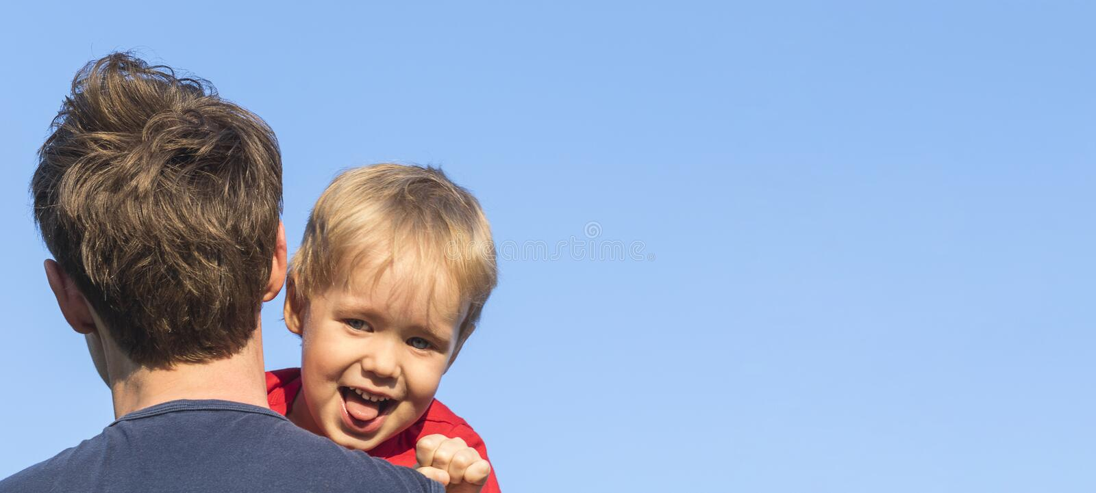 The father carries his son on his shoulder against the blue sky. Cheerful and funny little boy - blond looking at the camera and royalty free stock photos