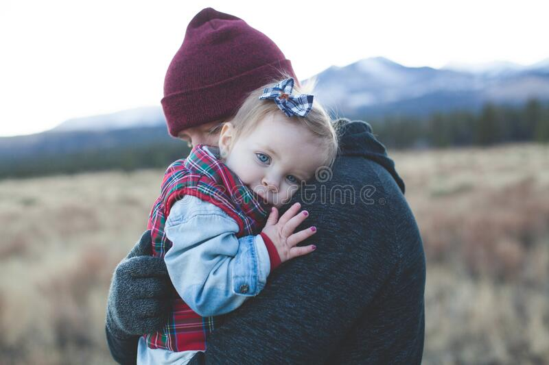 Father carrying baby daughter stock image
