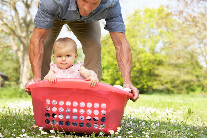 Father Carrying Baby Girl Stock Photo