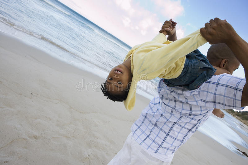 Father carrying daughter (5-7) on shoulders on beach, girl upside down, smiling, rear view (tilt) royalty free stock image