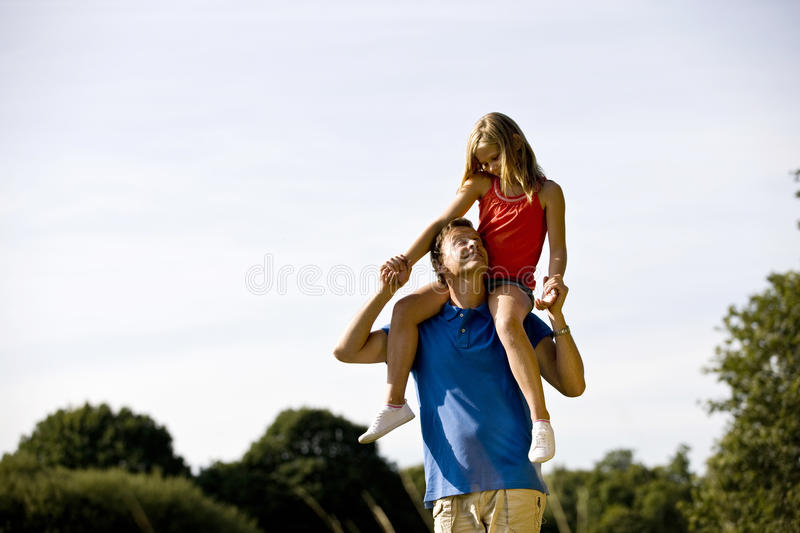 A father carrying his daughter on his shoulders royalty free stock photography
