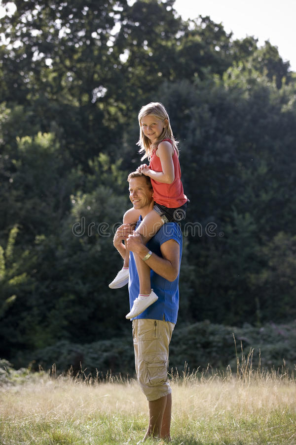 A father carrying his daughter on his shoulders royalty free stock photo