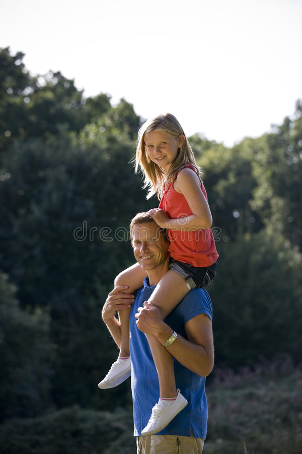 A father carrying his daughter on his shoulders stock photo