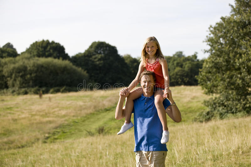 A father carrying his daughter on his shoulders stock images