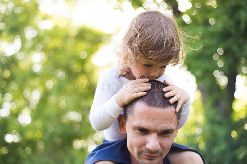 Father carrying his son on his shoulders. Sunny summer. stock images