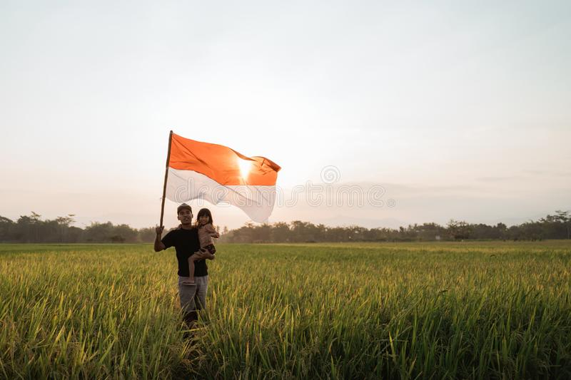 Father carrying little girl pride flapping Indonesian flag with happiness. In the rice field stock photo