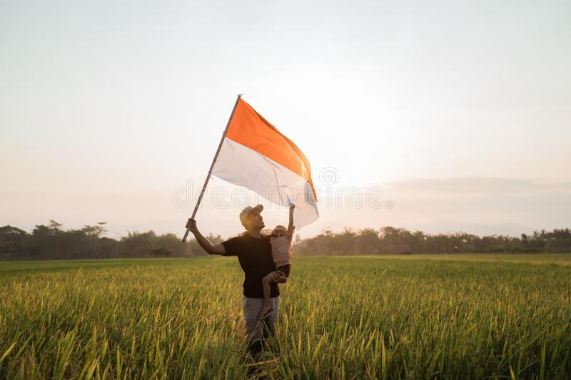 Father carrying little girl pride flapping Indonesian flag with happiness. In the rice field royalty free stock photos