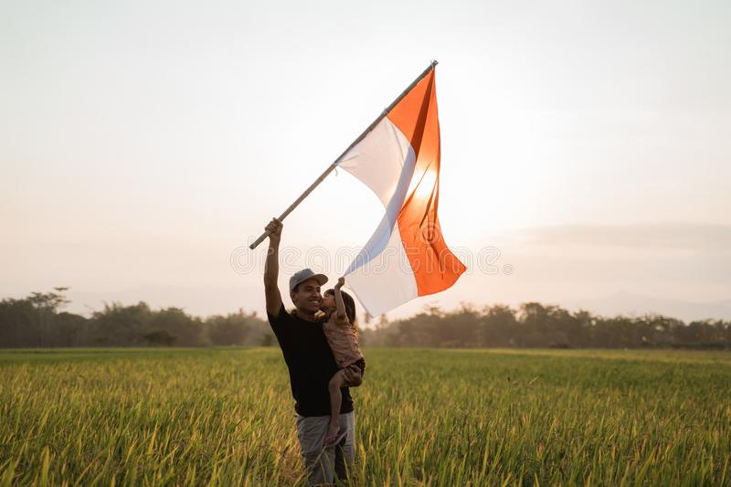 Father carrying little girl pride flapping Indonesian flag with happiness. In the rice field royalty free stock images