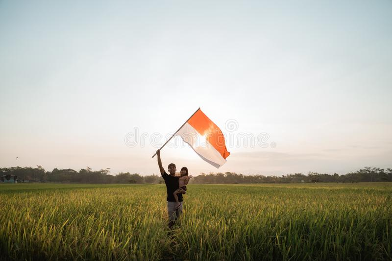 Father carrying little girl pride flapping Indonesian flag with happiness. In the rice field royalty free stock photography