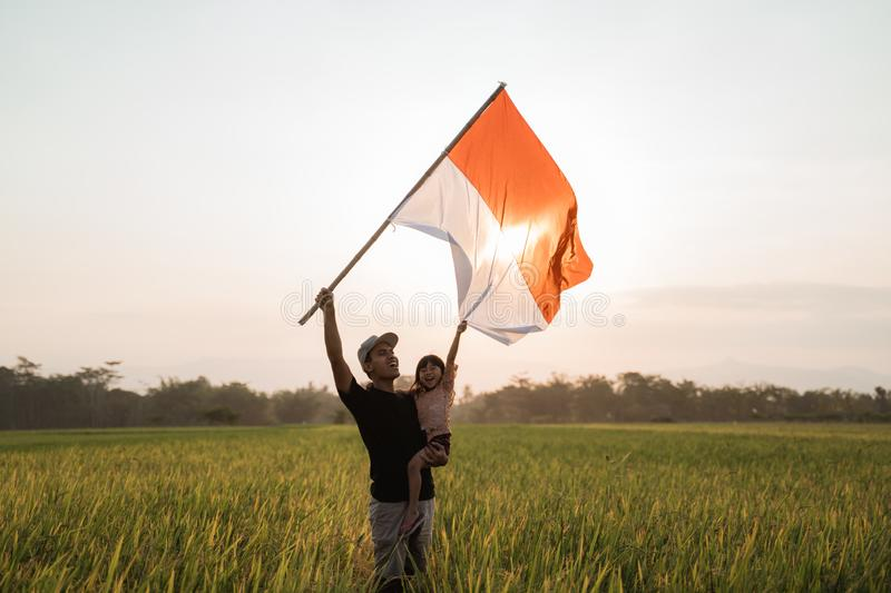 Father carrying little girl pride flapping Indonesian flag with happiness. In the rice field stock photos