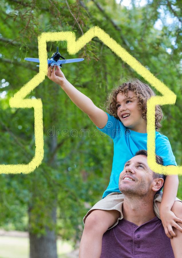 Father carrying son on his shoulders overlaid with house shape. Digital composition of a father carrying son on his shoulders overlaid with house shape royalty free stock image