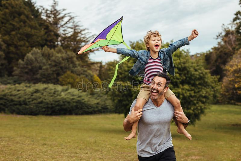 Father carrying son playing with kite in park stock image