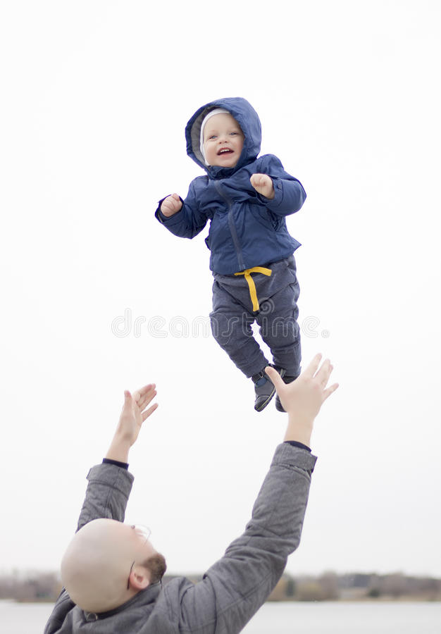 Father catching his baby son. Cute infant boy laughing and smiling. Outdoor shot. Family playtime royalty free stock photography