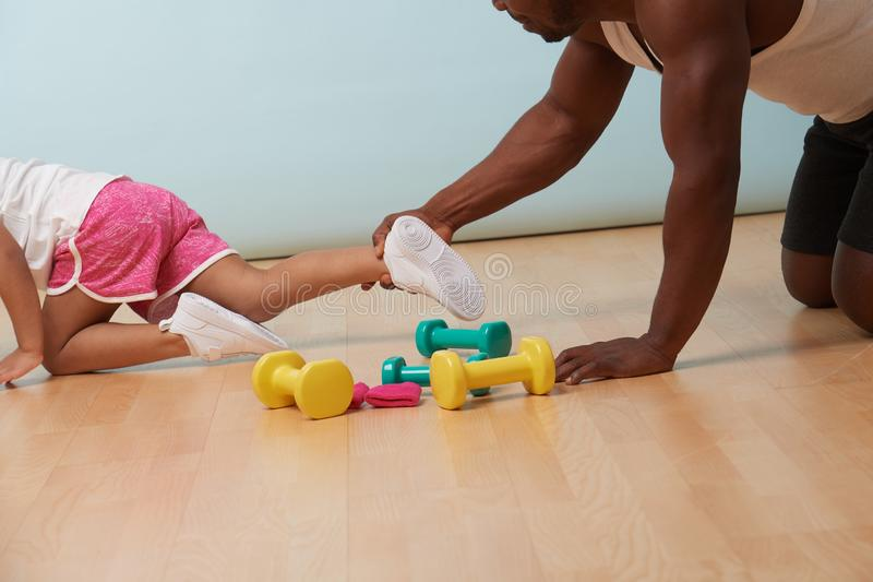 Father catching his little daughter`s leg as she tries to flee the exercise royalty free stock photography
