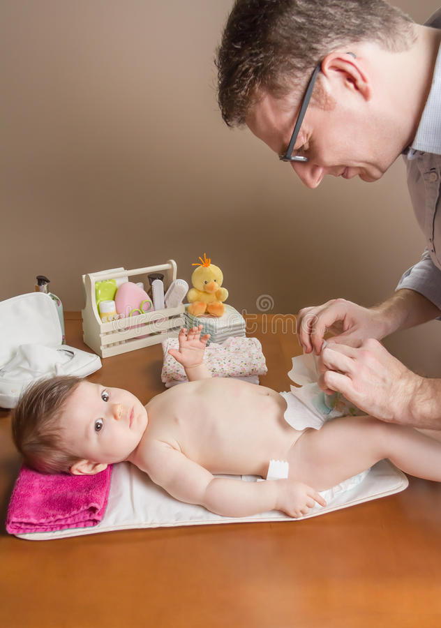 Father changing diaper of adorable baby stock photo