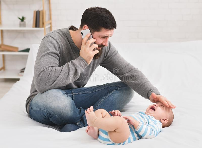 Father checking temperature and calling to doctor stock photography