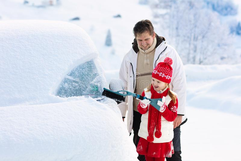Father and child brushing off car in winter stock photos
