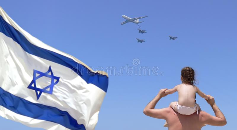 Independence Day of Israel. Father with child daughter on shoulders by sea beach watch on military aircrafts at festive air parade of Israel Army of Defense stock photography