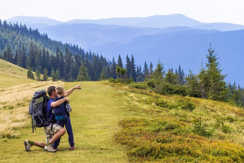 Father and child hiking in scenic mountains. Dad and son enjoying the view from the mountain top in Carpathian mountains royalty free stock photos