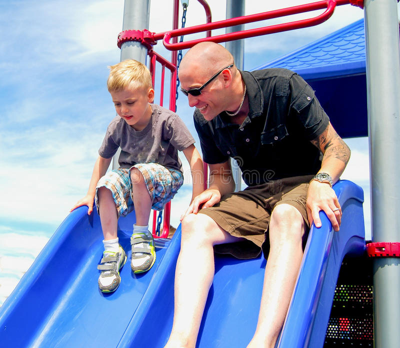 Father and Child on Playground Slide stock photography