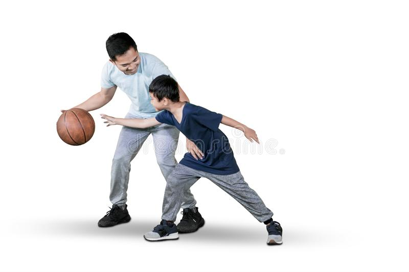 Father and child playing basketball on studio stock images