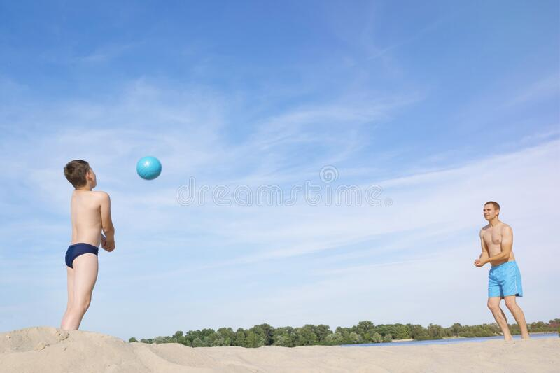 A father and a child are playing  Beach Volleyball.  Sports games on a sunny summer day.  The concept of an active lifestyle royalty free stock images
