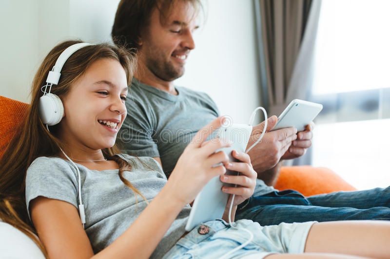 Father and child playing on tablet stock image