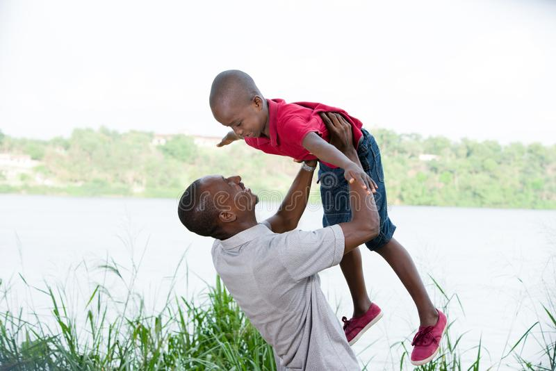 Father and child playing together outdoors stock photos