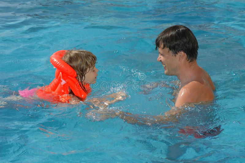 Father with child in pool royalty free stock image