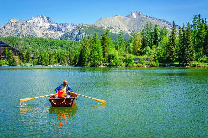 Father with child rowing in paddle boat. STRBSKE PLESO, SLOVAKIA - JULY 15, 2015: Father with child rowing in paddle boat on mountain lake with high peaks in royalty free stock photo