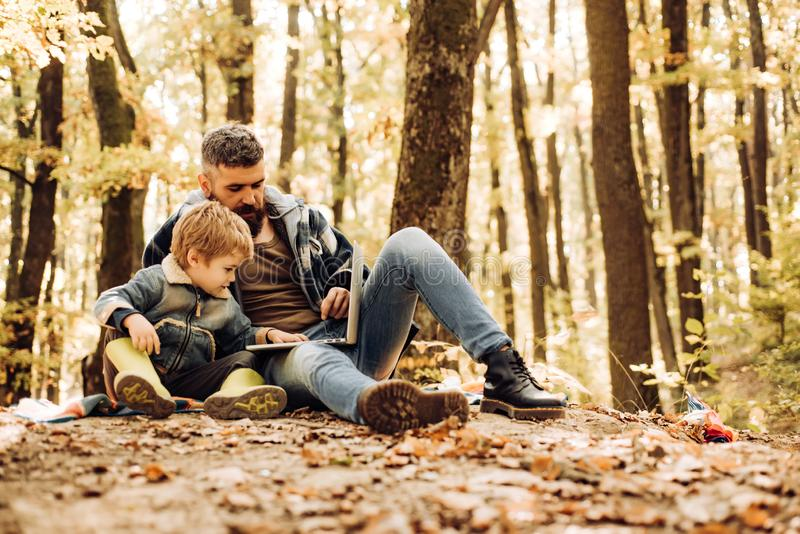 Father and child son in autumn park having fun and laughing. Parent teach baby. stock photo