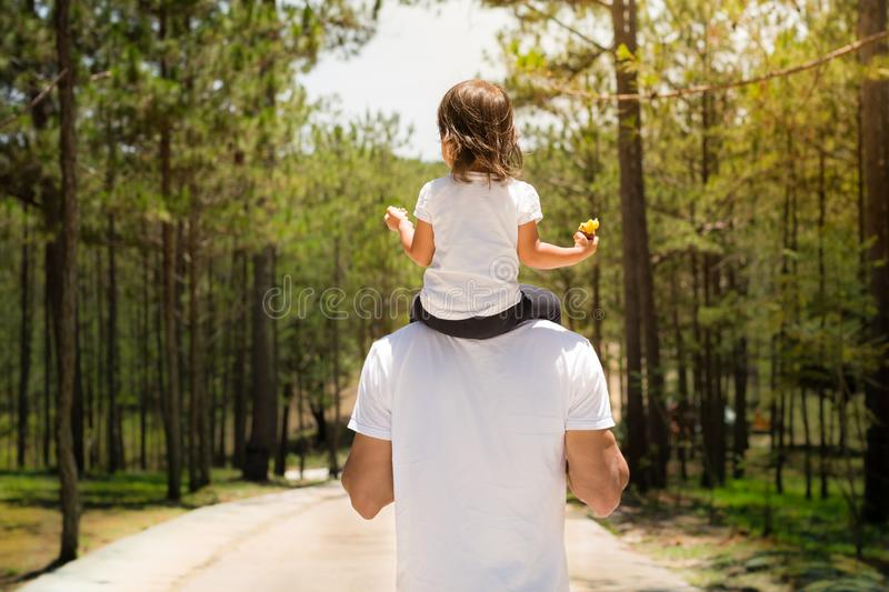 Father and child taking a walk together in a park outside. Green forest background royalty free stock image