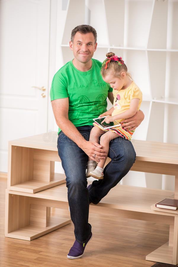 Father And Child Using Electronic Tablet At Home Stock Photo