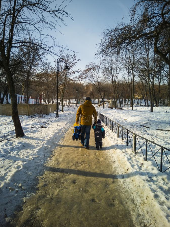 Father and child walk through the winter city park with sleds in hand royalty free stock images