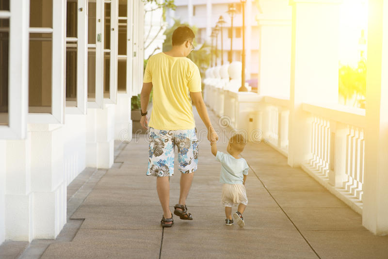 Father and child walking holding hands stock photo