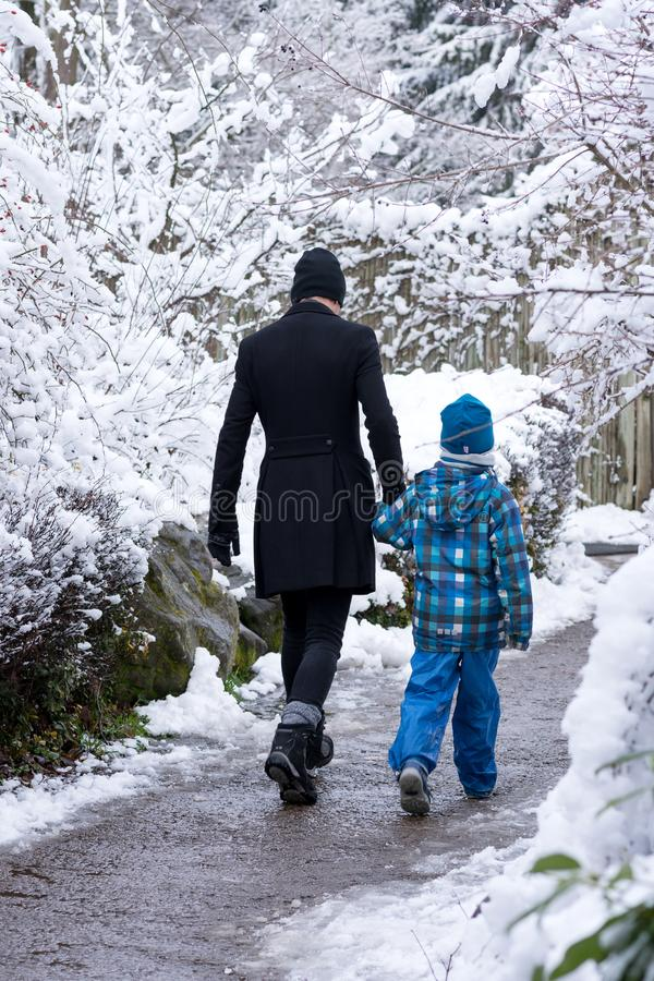 Father and child walking though winter park stock photography