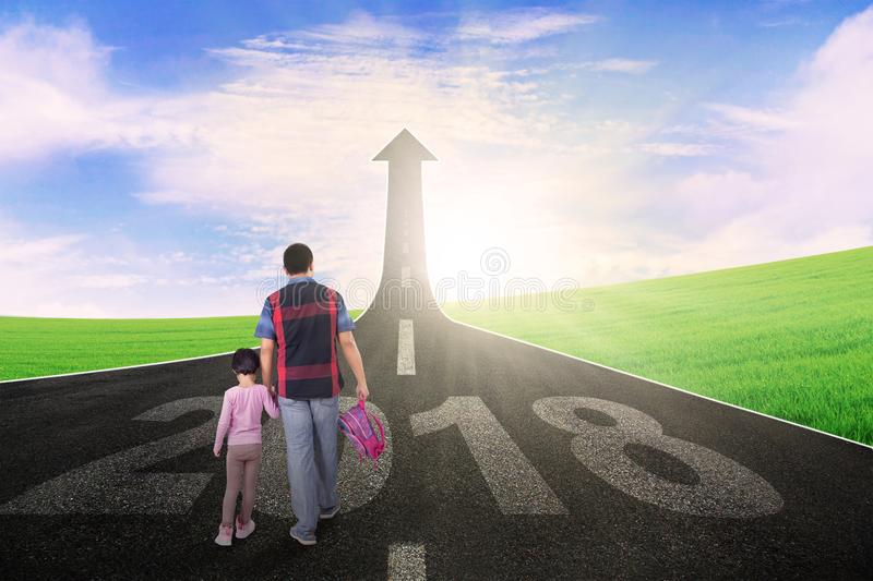 Father and child walking toward an upward arrow. Back view of young father with his daughter walking toward an upward arrow with numbers 2018 on the road stock image