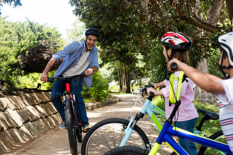 Father and children cycling in park. On a sunny day stock image