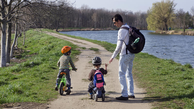 Father and children cycling. Father with children on a cycling path along a river royalty free stock photography
