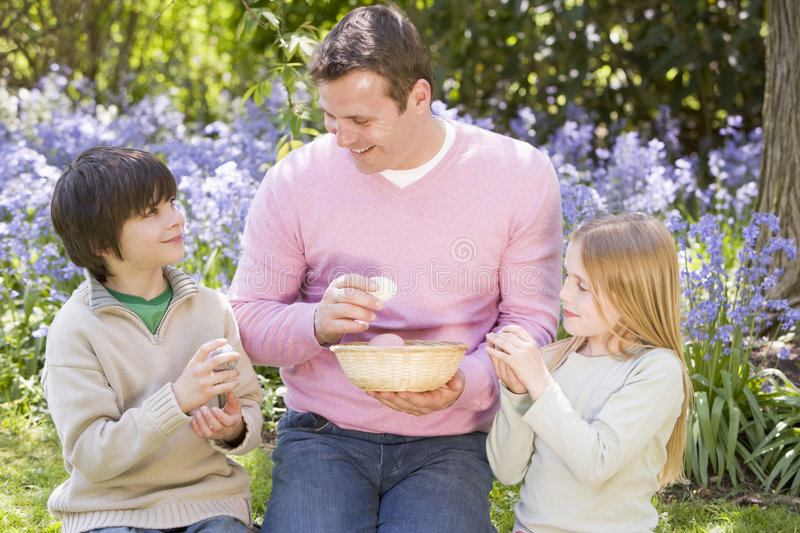 Father And Children On Easter Look For Eggs Royalty Free Stock Photo