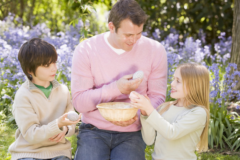 Father and children on Easter looking for eggs stock photos