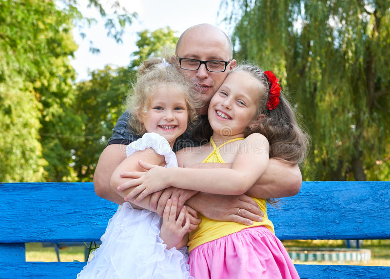 Father with children in park, happy family portrait, group of three peoples sit on bench, parenting concept stock photos