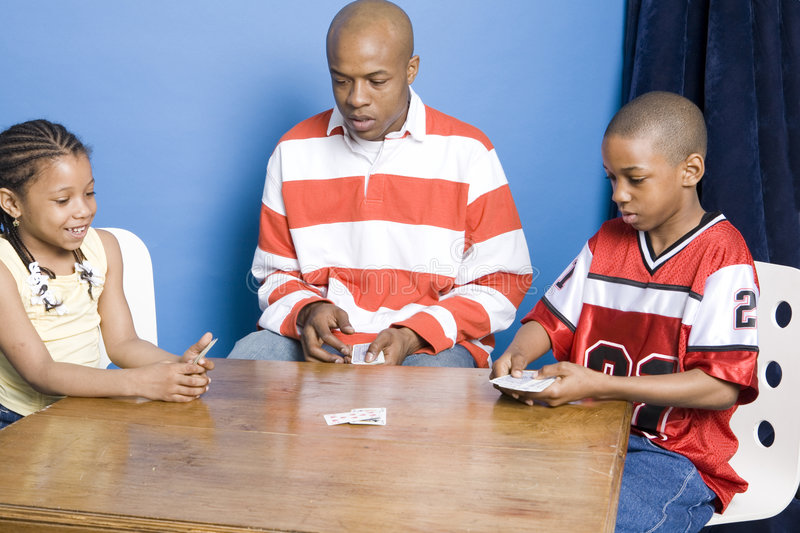 Father and children playing cards. Family playing cards at home royalty free stock photos