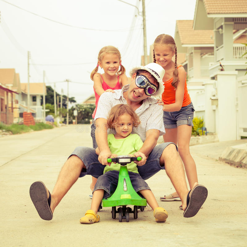 Father and children playing near a house stock photos