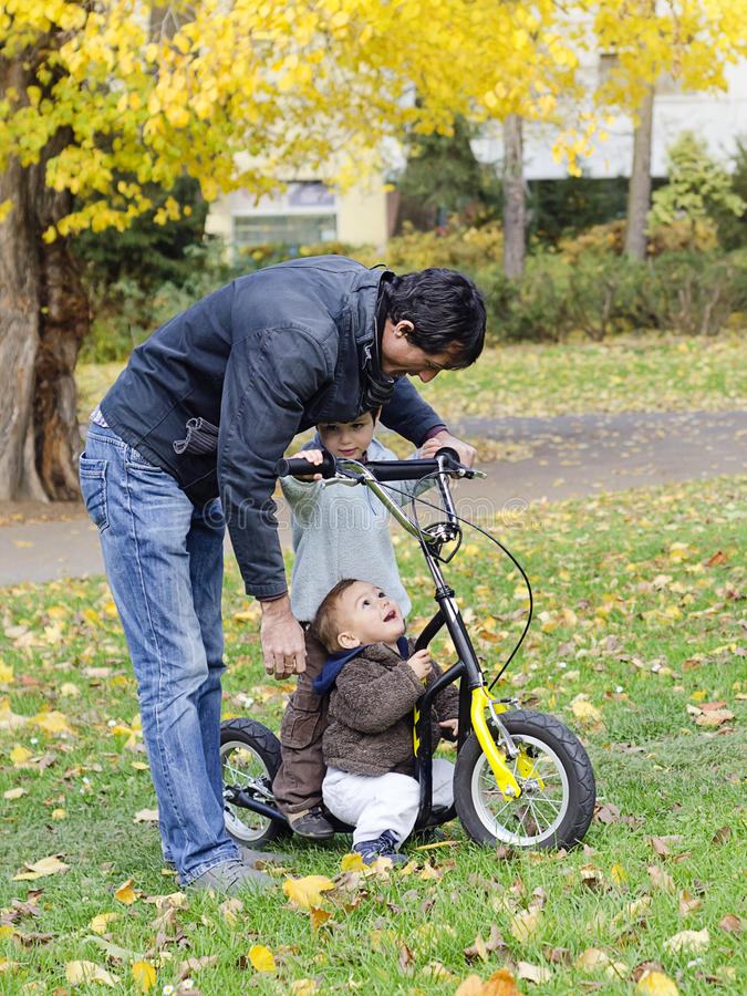 Father with children on scooter stock photos