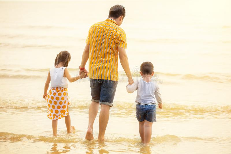 Father And Children  walking into the  Beach Holiday .  two kids one dad . rear back view stock images