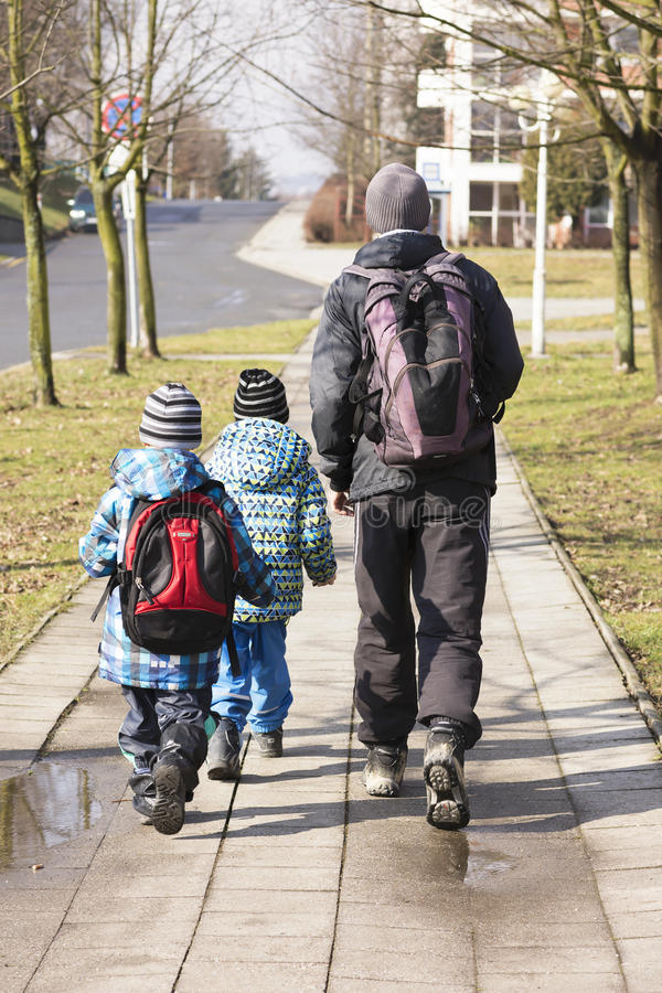 Father and children walking on the street royalty free stock photography