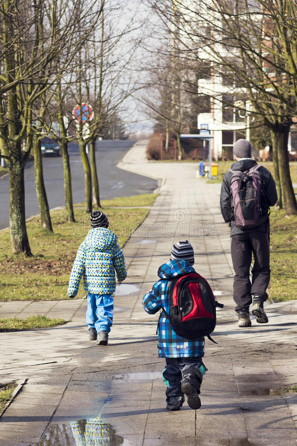 Father and children walking on the street royalty free stock photo