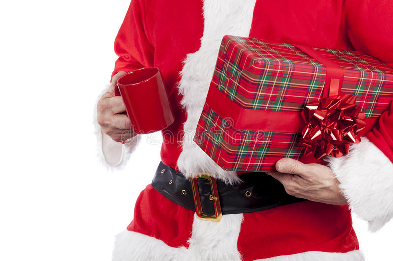 Father christmas carrying a red bowed present and having a cup of tea. On a pure white background royalty free stock photos